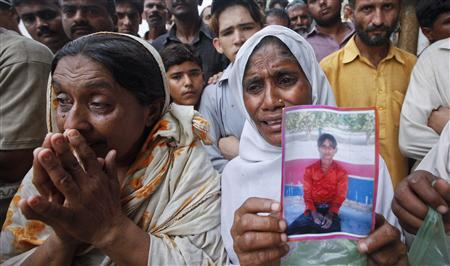 A woman holds a portrait of her son while waiting with others to identify his body, after a fire at a garment factory in Karachi