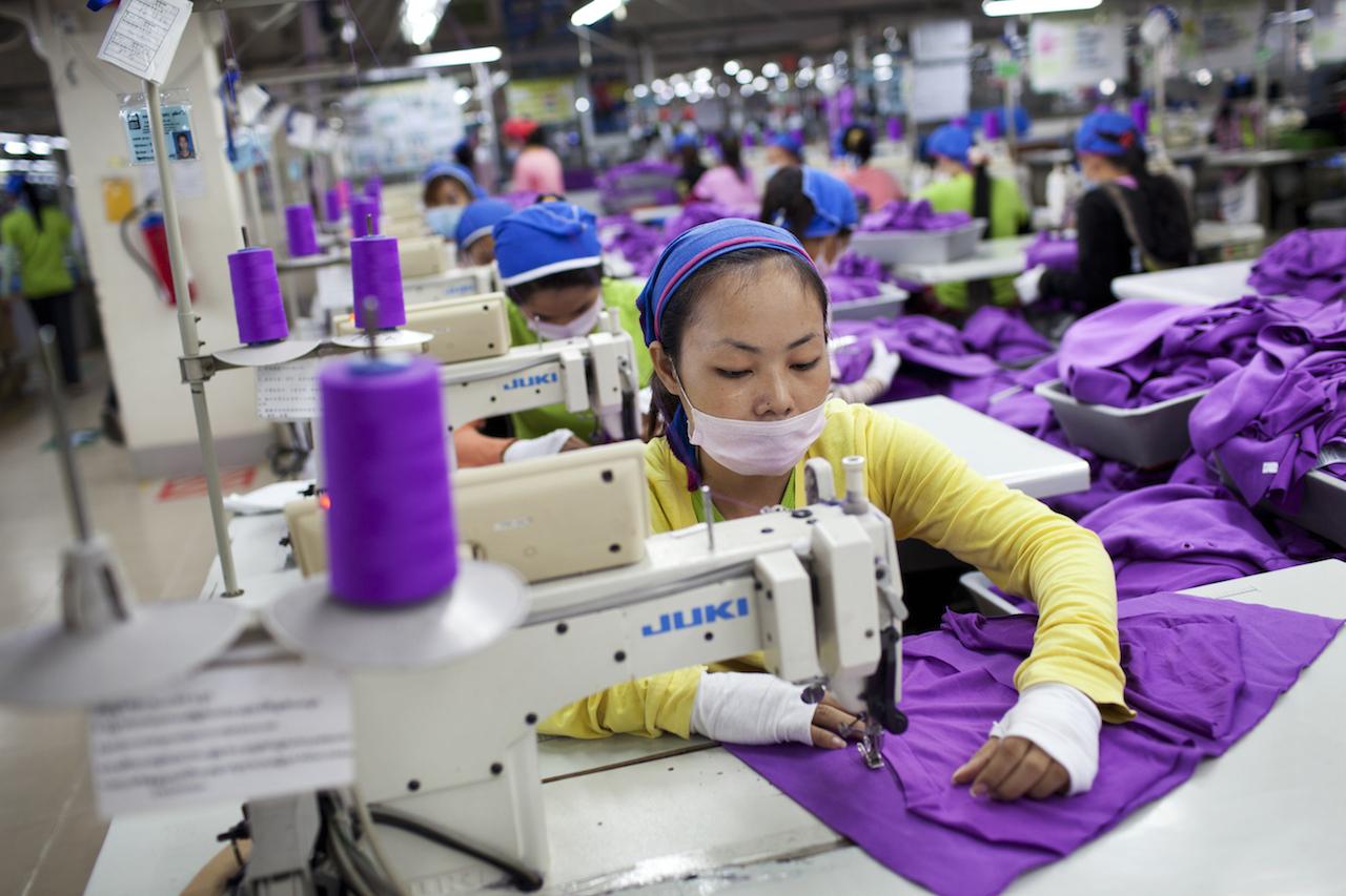 Hundreds of Asian women sewing purple material inside a factory (sweat shop)